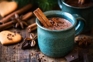 Hot-chocolate-with-a-cinnamon-stick-anise-star-and-grated- chocolate- topping-in-festive- Christmas- setting-on-dark-rustic-wooden- background-UNAMGlobal