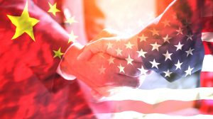 Businessman-shake-hand-over-United-States-of-America-and-China-flag-UNAMGlobal